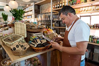 Store owner taking inventory on mobile device
