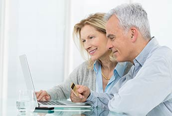 Middle aged couple at a laptop with a debit card