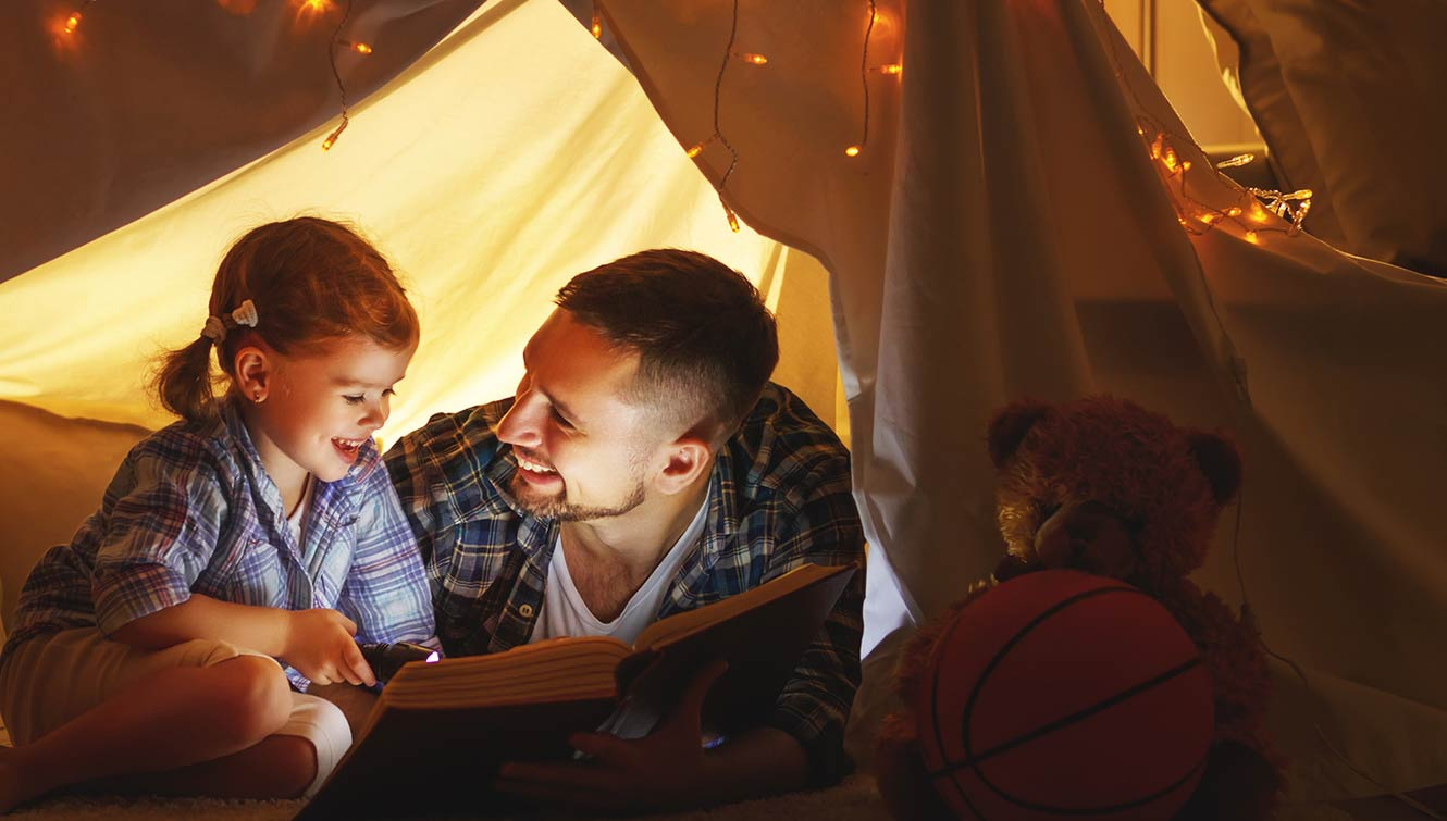 Father and daughter reading in a fort.